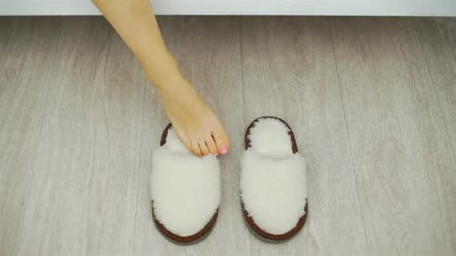 Closeup of Woman Putting on Slippers