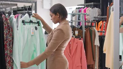 Fashion African Female in a Clothing Store Chooses a Sweaters to Buy Woman Shopping for Clothes