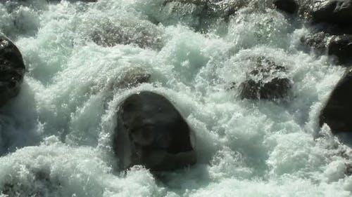 Foamy Stream Flowing in Wild Valley
