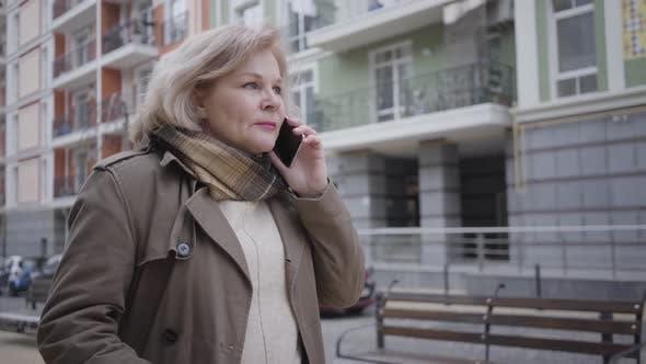 Thumbnail for Portrait of Mature Elegant Caucasian Woman Walking on City Street and Talking on the Phone. Senior