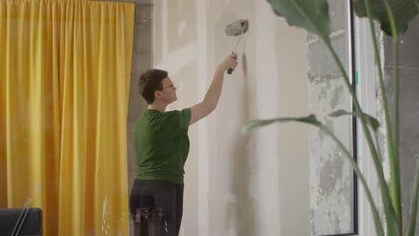 Woman Paint Wall in Her Room in Grey DIY Home Repair