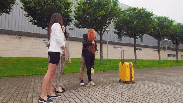 Thumbnail for Girl with Red Hair Says Goodbye and Hugs with Friends Going on a Business Trip. Friends Accompany