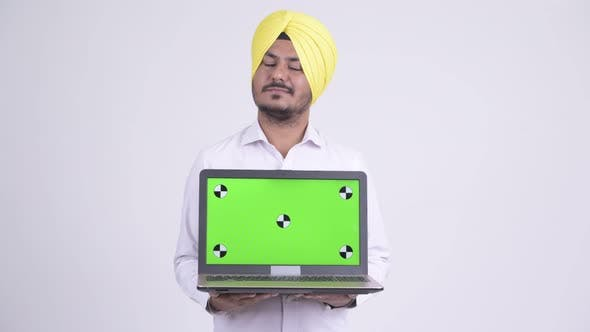 Thumbnail for Happy Bearded Indian Sikh Businessman Thinking While Showing Laptop