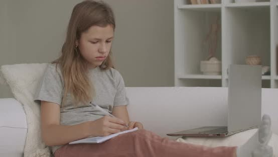 School Girl Is Listening Teacher By Laptop and Writing at Exercise Book, Sitting on Couch at Home, e