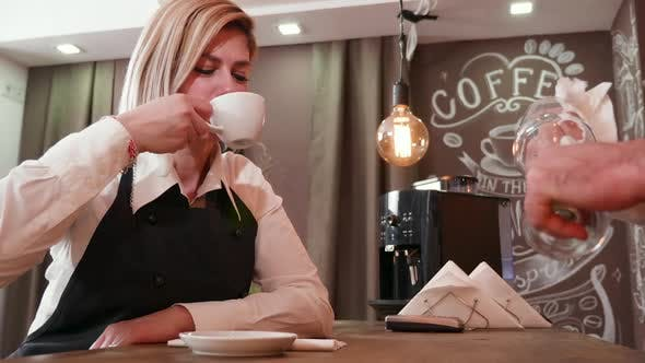 Thumbnail for Female Waitress Drinks Coffee and Uses a Paper Napkin