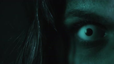 Terrifying creepy zombie woman, close up of white eye opening. Scary look.