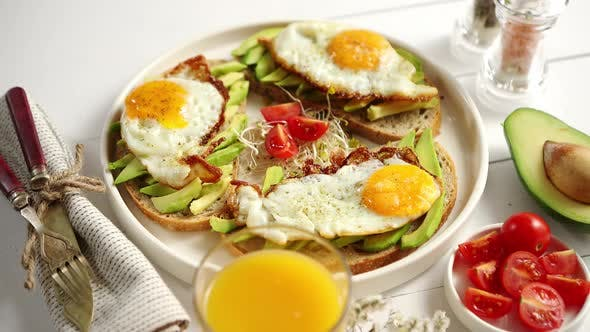 Thumbnail for Delicious Healthy Breakfast with Sliced Avocado Sandwiches with Fried Egg
