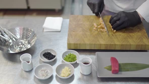 Cover Image for Hands of Chef in White Restaurant Uniform Cutting Small Salmon Fish