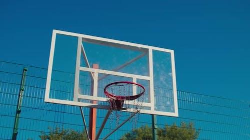Basketball Rim with Glass Backboard Against Blue Sky
