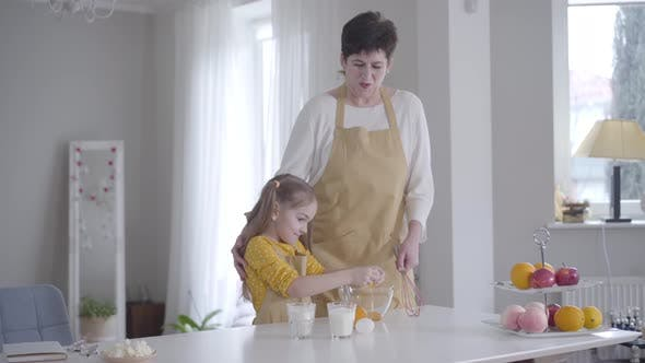 Thumbnail for Little Cute Caucasian Girl Breaking Egg Into Bowl and Smiling. Happy Granddaughter Helping
