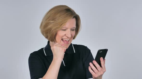 Cover Image for Old Woman Excited for Success While Using Smartphone