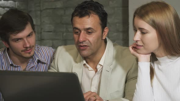 Thumbnail for Mature Businessman and His Younger Colleagues Working Together on the Laptop