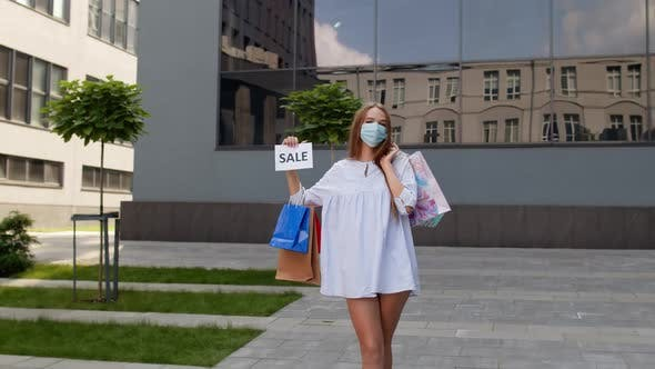 Thumbnail for Girl in Protective Mask with Shopping Bags Showing Sale Word Inscription During Covid-19 Pandemic