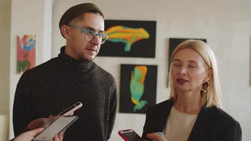 Woman and Man Giving Interview to Press in Art Gallery