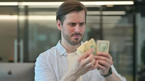 Portrait of Man Feeling Worried Counting Dollars