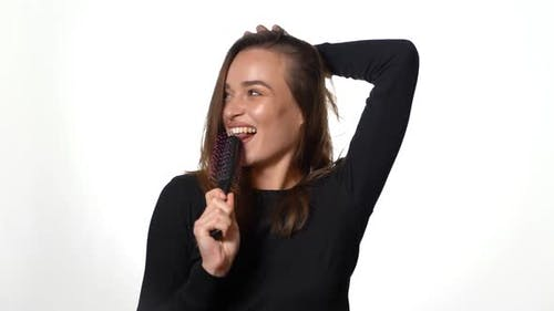 Smiling lady in black jumper and with long hair is holding a hairbrush in the studio