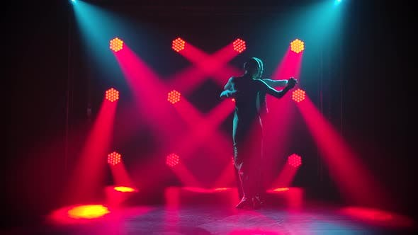 Professional Couple Dancing Tango in the Studio with Red Spotlights. Young Woman and Man Dance Latin