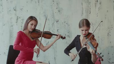 Duet of Admiring Female Musicians in Dresses Playing the Violins Indoor