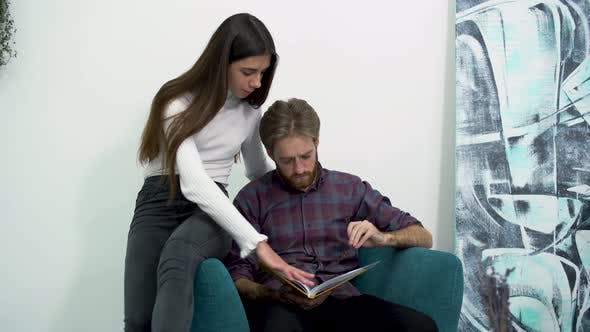 Cover Image for Two Young Beautiful Girls and Handsome Bearded Guy Are Reading a Book While Sitting in a Chair