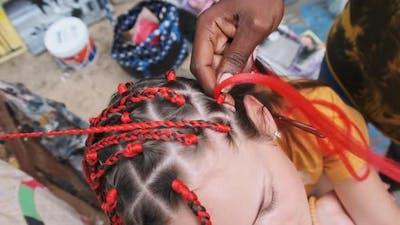 Process of Weaving African Braids with Red Kanekalon Outdoor Zanzibar Africa