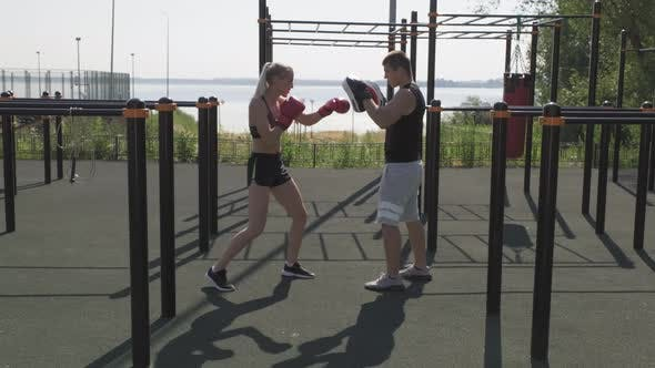 Woman Practicing Boxing Punches With Male Coach