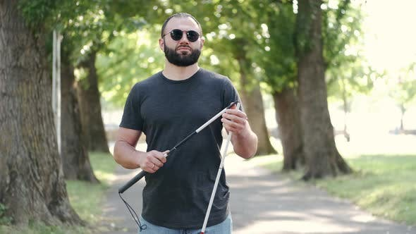 Thumbnail for Disabled Man Folding a White Cane in a Park