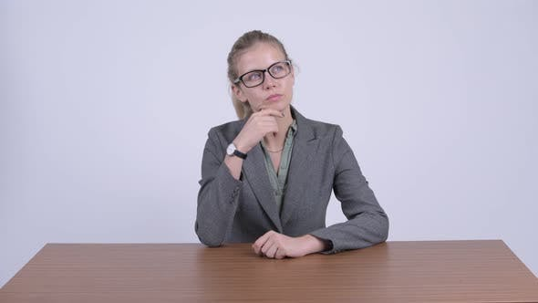Cover Image for Young Beautiful Blonde Businesswoman Thinking While Sitting Behind Desk