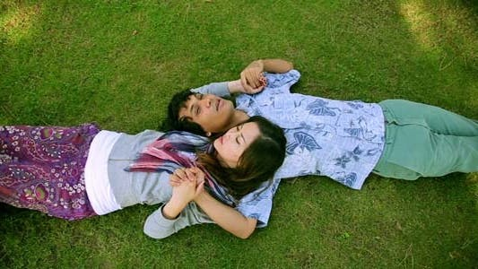 Thumbnail for Young Couple Relaxing On Lawn In A City Park