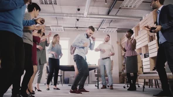 Thumbnail for Young Caucasian Employee Dancing with Colleagues, Celebrating Business Achievement at Casual Office