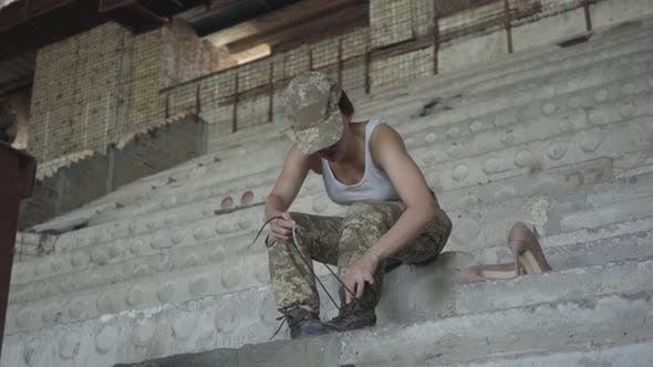Thumbnail for A Young Woman in Military Uniform Sitting on the Cold Concrete Stairs in the Abandoned Building