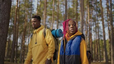 Afroamerican Couple Hiking Trekking in Forest with Backpacks Enjoying Their Adventure Tourism