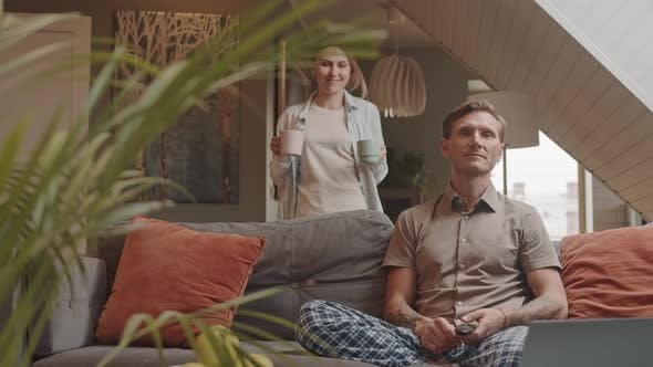 Wife Bringing Coffee to Man on Couch