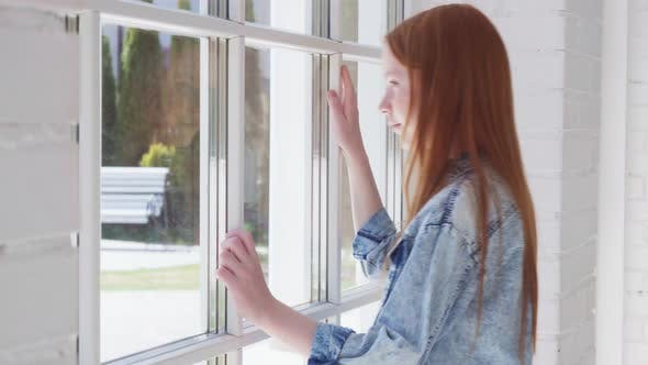 Teenage Girl Looks Out Window with Curiosity
