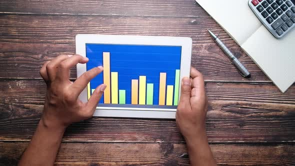 Thumbnail for Analyzing Bar Chart on Digital Tablet at Office Desk, Using Self Created Chart