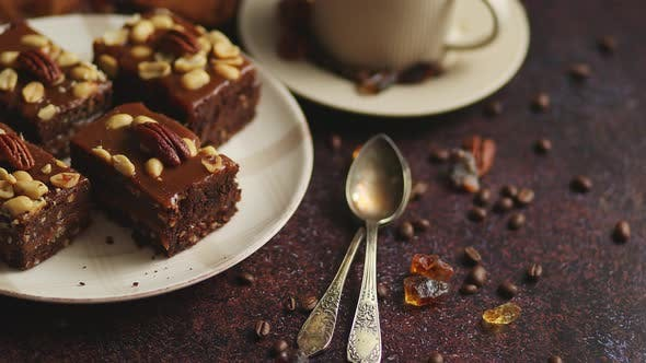 Thumbnail for Chocolate Cake with Caramel Frosting, Pecans and Hot Coffee, on Rustic Background. Freshly Baked