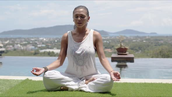 Thumbnail for Lady Practicing Yoga in Lotus Pose Against Ocean Coast