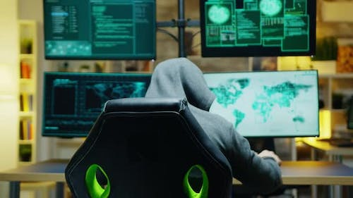 Masked Hacker in His Apartment Looking Into the Camera