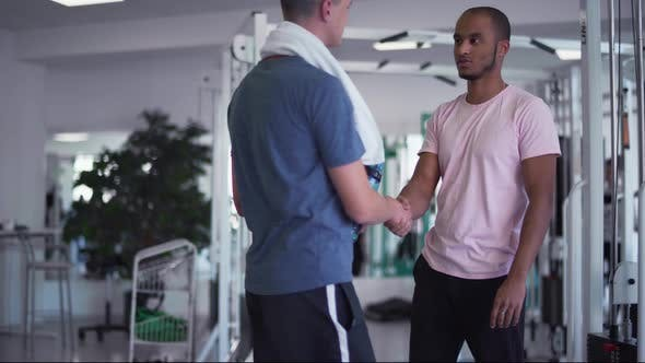 Thumbnail for African American Guy Shakes Hands with a Caucasian Guy in the Gym Two Young Guys in the Gym People