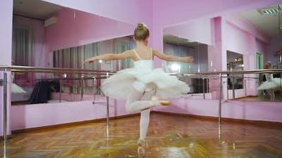 Ballerina dancing in studio in front of mirror. In the ballet hall. A little dancer.