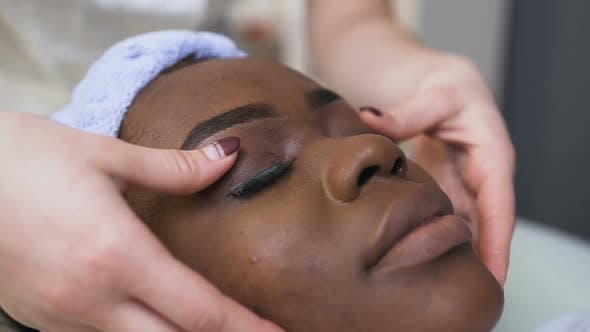 Thumbnail for Female Beautician Hands Making Massage on African Female Face and Eyes