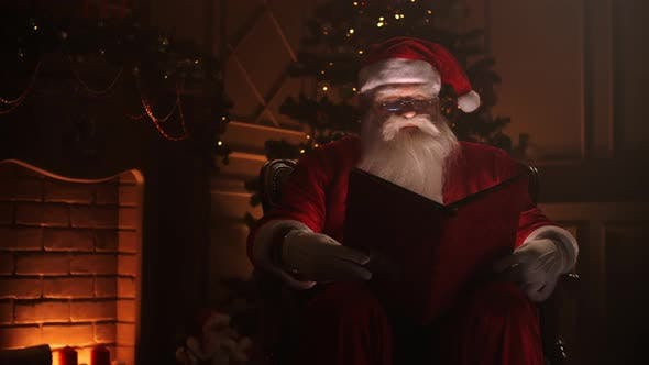 Cover Image for Joyful Santa Clause Sitting in His Rocker in Decorated Room, Reading a Book with Red Cover - Holiday