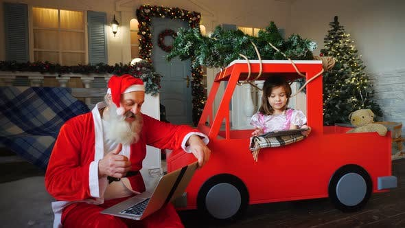 Thumbnail for Santa Claus Makes Thumbs Up Working with Laptop and Little Girl Enjoying with Presented Tablet.