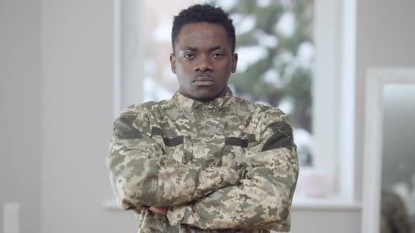 Confident Serious African American Military Man in Camouflage Uniform Crossing Hands Looking at