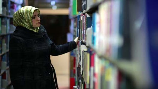 Female Student Wandering Between Shelves