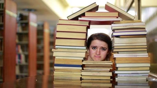 Thumbnail for Student Gazing Through House-Shaped Stack Of Books