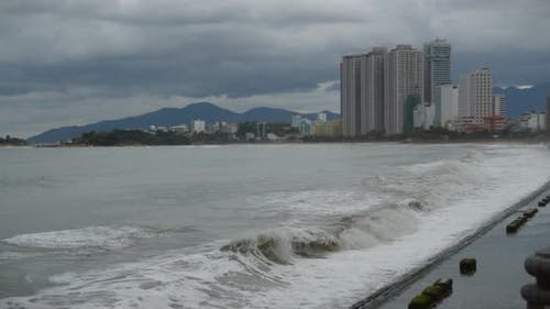 Cloudy Weather, Rain, Large Gray Clouds, Gloomy Weather, Sea Waves Break on the Shore of the City