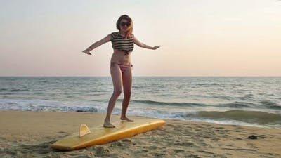 Woman Balancing On Surfboard