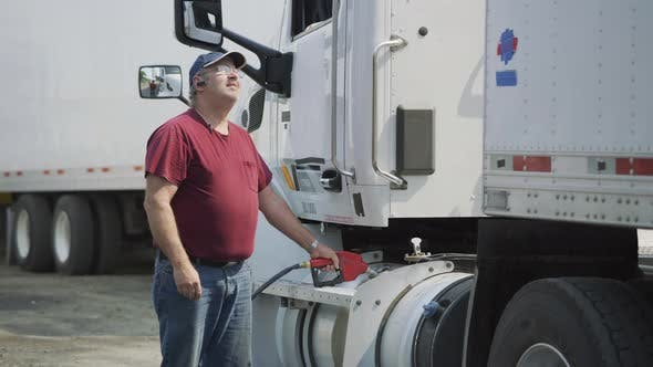 Truck driver filling up fuel tank of semi truck.  Fully released for commercial use.