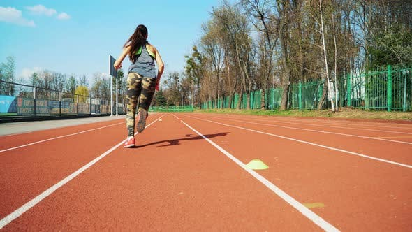 Thumbnail for Young woman go in for sport run at the stadium track in the morning