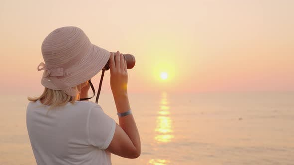 Thumbnail for A Young Traveler in a Hat Looks Through Binoculars To the Pink Sea, Where the Sun Rises. Romance and